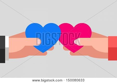 Man's and woman's hands are keeping blue and pink hearts and tending to one another. Intersection of two hearts. Heterosexual couple in love