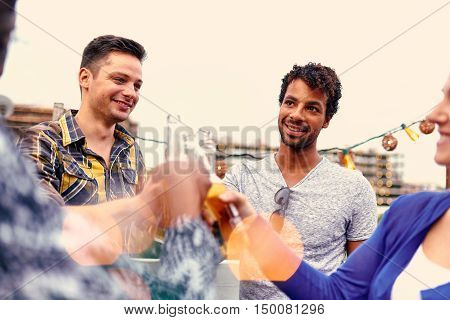 Four young casual friends having fun at an urban party and having a drink with cityscape view