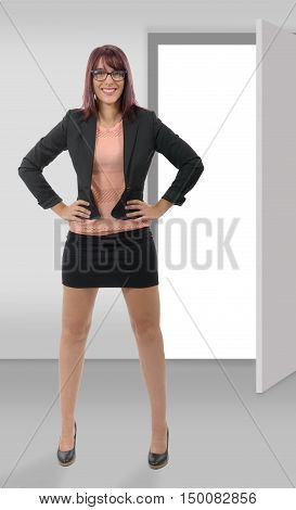 A happy young business woman standing in office