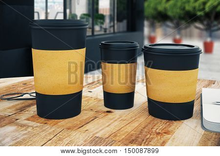 Close up of three black take away coffee cup with blank brown paper holder placed on wooden table. Cafe exterior background. Mock up 3D Rendering