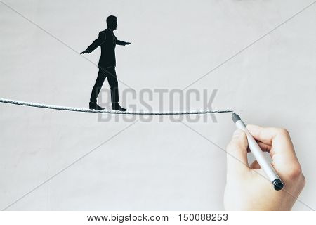 Businessman silhouette walking on rope that is being drawn by male hand. Conceret background. Balancing concept