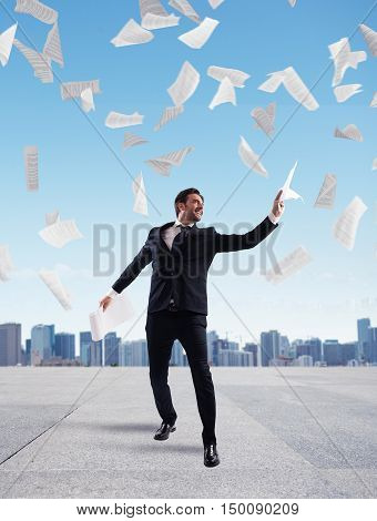 Businessman in a roof of skyscraper rejoices throwing sheets