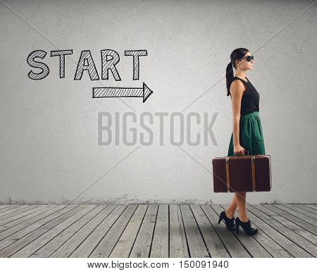 Businesswoman with suitcase ready to walk in the direction of the arrow