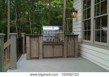 Gas grill on deck with trees in background