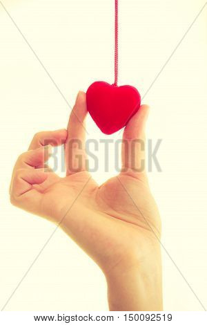 Love and help. Smoothy female hand with sign symbol of charity and fondness. Palm with red little heart.