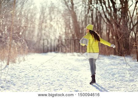 Winter happy woman walking in snow outdoors nature. Joyful young lady having fun on an outdoor walk activity on forest path wearing yellow outerwear jacket with warm boots, scarf, hat.