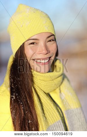 Winter season girl smiling outside in snow. Portrait of Asian woman happy outdoors with healthy smile on sunny wintertime day wearing yellow hat and scarf outerwear fashion outfit.