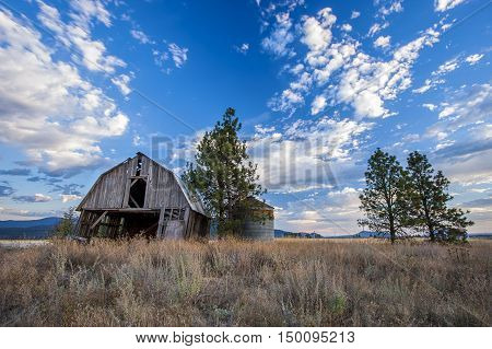 Old barn under a blue sky with clouds in the Rathdrum Prairie in north Idaho.