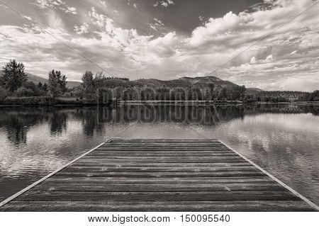 A B&W image of a wood dock by the Coeur d'Alene River near Cataldo Idaho.