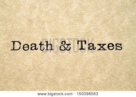 """A close up image of the word """"death & taxes"""" from a typewriter on antique paper"""