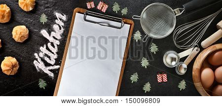 Blank clipboard with kitchen utensils and christmas toys on black background copy-space.