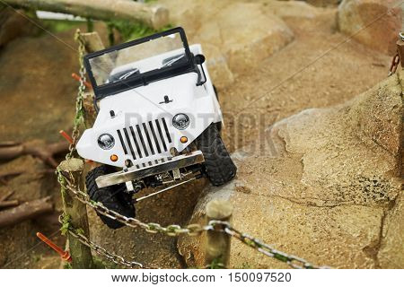 MOSCOW, RUSSIA - APR 02, 2016: Toy model of car has an accident on mountain rocky road in recreational zone Arena of Aviapark shopping center. Aviapark shopping area - 230 000 sq.m.