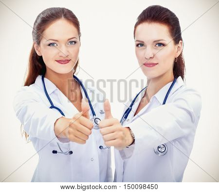 Two young woman doctor showing ok , standing in hospital
