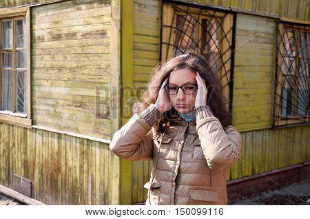 Girl in glasses clutching her head in her hands