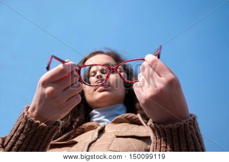 Teen girl try on glasses offers against the blue sky