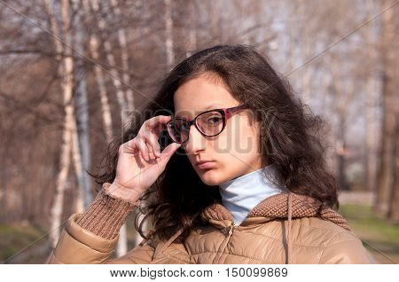 Portrait of a girl with glasses in the park
