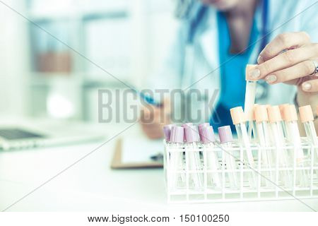 Woman researcher is surrounded by medical vials and flasks, isolated on white background