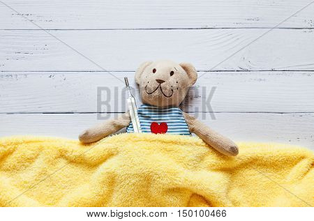 children's soft toy teddy bear in bed with thermometer and pills, take the temperature of a mercury glass thermometer. On a white wooden background. Playing in hospital. child's illness.