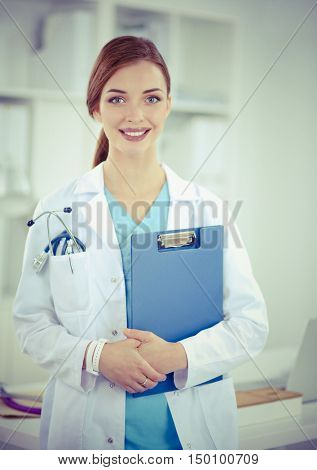Smiling female doctor with a folder in uniform standing at hosp