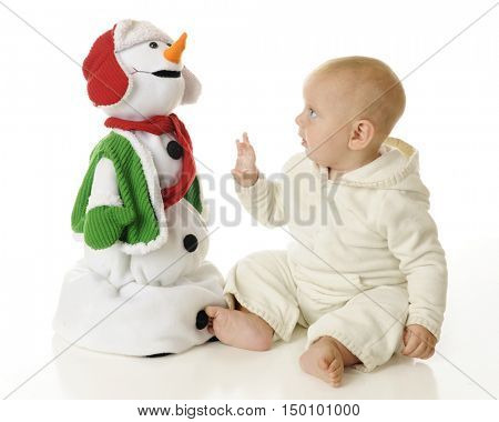 An adorable baby boy looking up skeptically at a toy Christmas snowman, wondering if he is touchable.  On a white background.