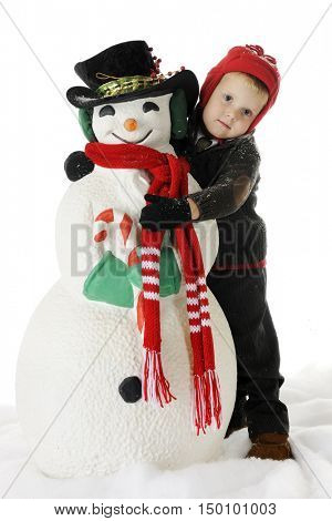 An adorable preschooler hugging his snowman.  On a white background.
