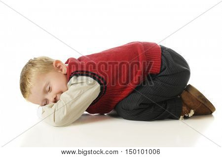 An adorable preschooler in slacks and a sweater vest, bottoms up feigning sleep.  On a white background.