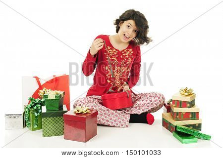 A pretty teen in her pajamas delightedly tying up (or untying) a red gift box.  On a white background.