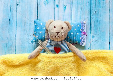 children's soft toy teddy bear in bed with thermometer and pills, take the temperature of a mercury glass thermometer. On a blue wooden background with a yellow blanket. Playing in hospital.