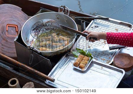 Fried spring roll shop on boat at Damnoen Saduak floating market.