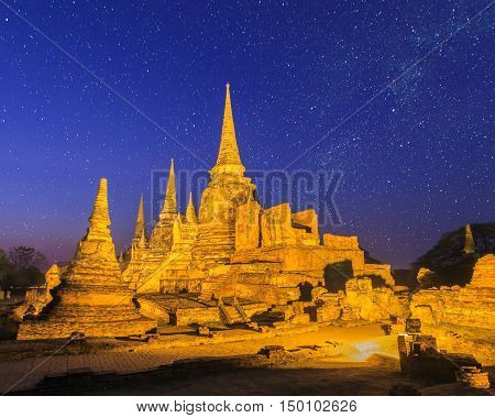Asian religious architecture. Ancient pagoda at Wat Phra Sri Sanphet temple under stars and space dust in the sky Ayutthaya Thailand