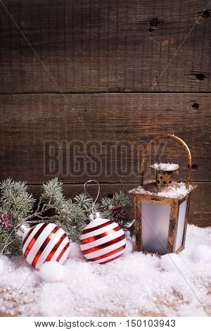 Christmas balls decorative lantern and branches fur tree on aged wooden background. Decorative christmas composition. Selective focus. Place for text. Vertical image.