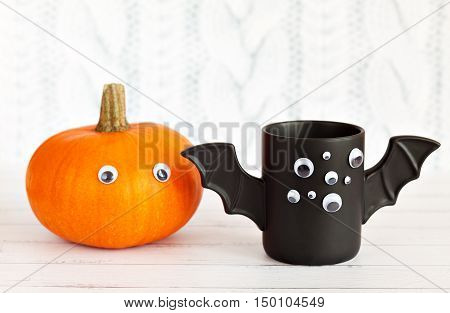 A cup of coffee like a bat with eyes on Halloween on a white background. Pumpkin with eyes. Toy bat. Halloween concept