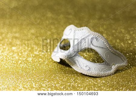Female carnival mask with bokeh on golden background