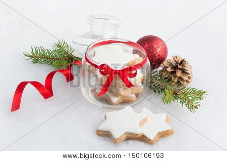 Close up of a glass jar full with christmas homemade star cookies over white fluffy background. Christmas decoration