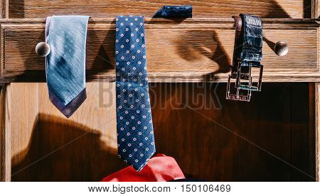 Male fashion stylish clothes in home wardrobe. Neckties and belts