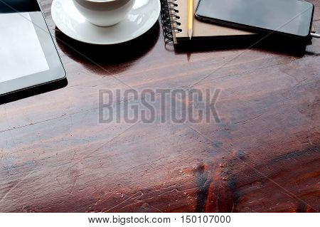 Mobile devicescoffee and note book on wooden table.