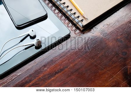 Mobile devices and notebook on wooden background.