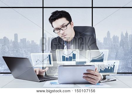 Young Arabian businessman looks busy working in the office with laptop and virtual financial statistic on digital tablet