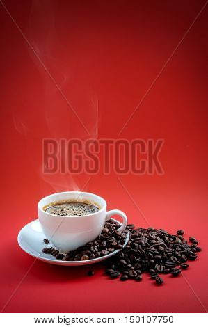 Coffee beans and red coffee cup on red background