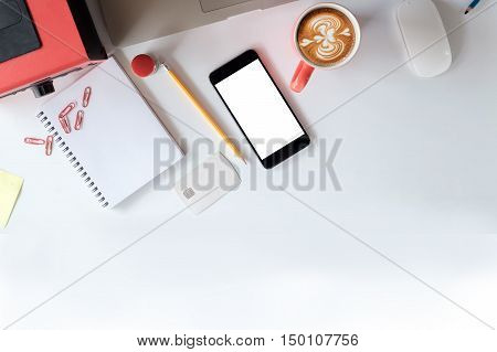 White desk with office supplies and cup of coffee top view