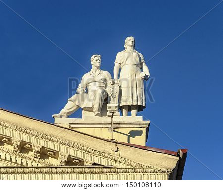 Minsk, Belarus - September 13, 2016: Sculpture of man and women on the roof of Trade Union Palace. Stalin's era style.