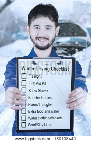 Male Arabian mechanic showing clipboard with winter driving tips and smiling at the camera