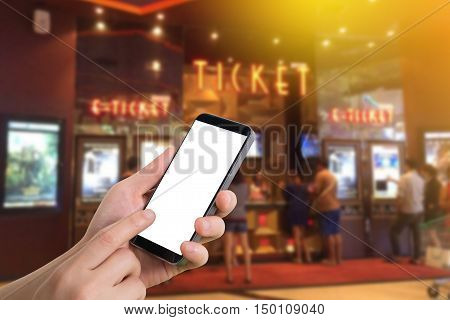 human hand hold and touch smartphone tablet cell phone with blank screen on blurry theater Online booking ticket concept.