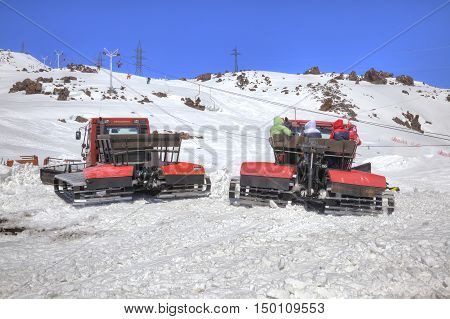 CAUCASUS RUSSIA - May 01.2015: Snow grooming with passengers in a basket goes by the second level of mountain Elbrus