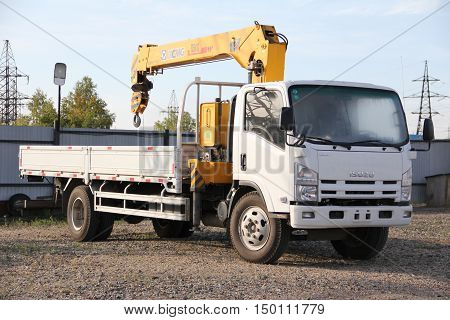 White Isuzu flatbed truck with a crane arm is in the parking lot - Russia, Moscow, 21 September 2016