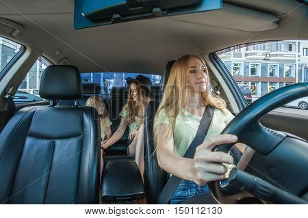 blonde beautiful woman with a smile driving a car. Her cute daughters sitting on rear
