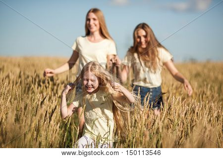 happy mother and her daugthers run on wheat field