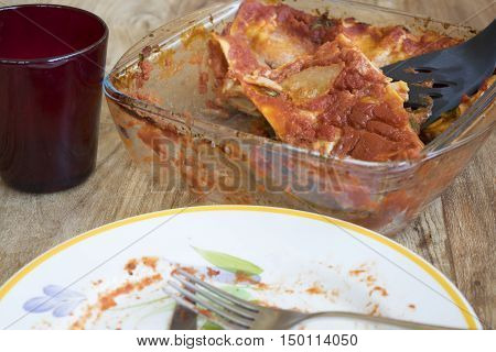 eating lasagne with leftovers and used dishes