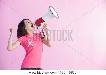 Happy woman hold microphone with pink ribbon great for prevention breast cancer concept