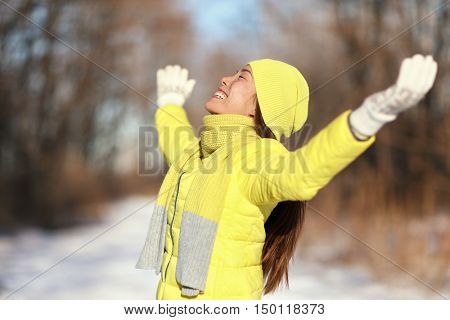 Happy snow freedom carefree woman. Relaxing Asian woman soaking up the sun on a sunny winter day with arms up in forest nature outdoors in yellow down jacket with knit hat and warm scarf.
